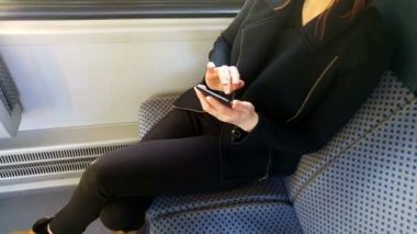Woman sitting on a train using her phone