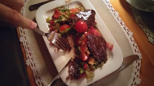 ein Mann isst in einem Restaurant einen Snack mit Fleisch und Gemüse