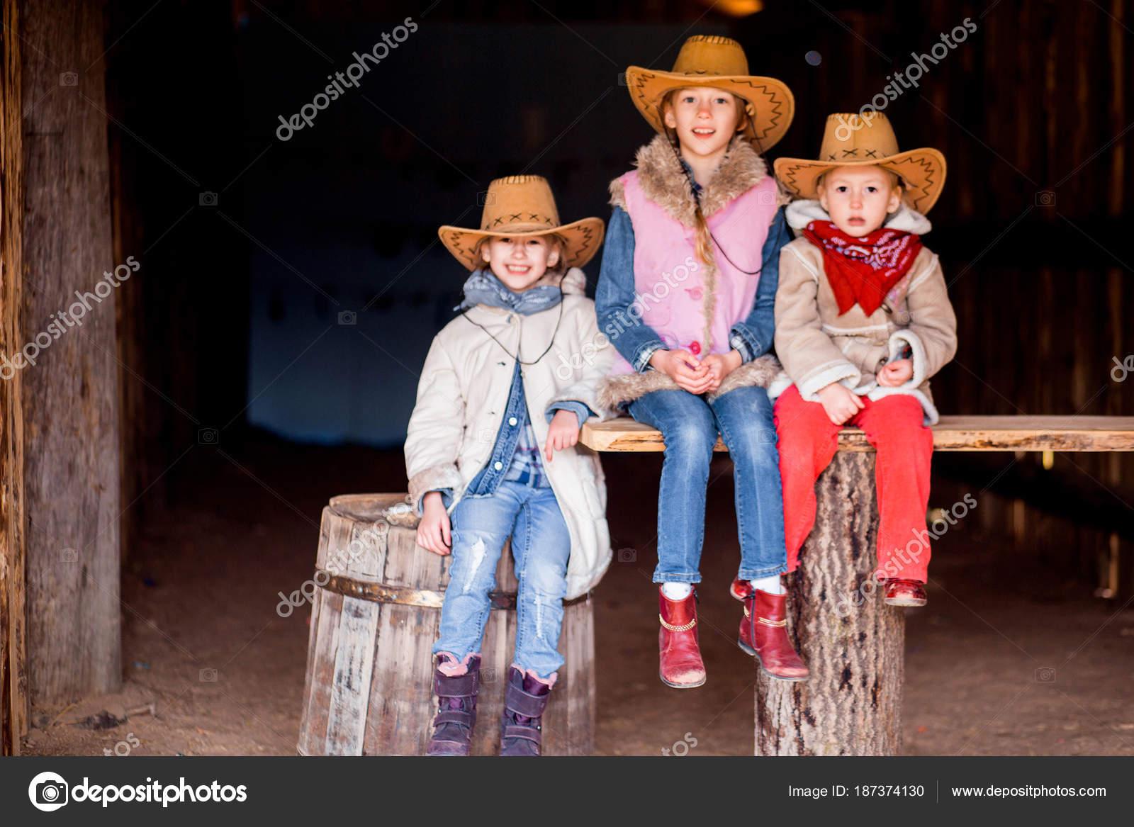 Tres hermanas vestidas con estilo vaquero sentarse en un banco en un  granero — Foto de 39bd48b50b6c