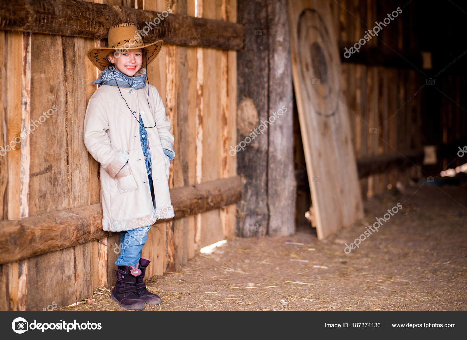 A little girl in a cowboy hat stands near the wall of a barn– stock image 344153ce6d89