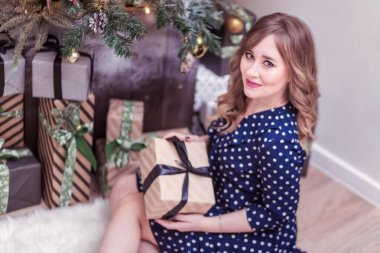 Beautiful woman in a blue dress sits near a New Year tree with a gift in her hands