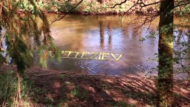 The inscription of green apples floats along the river. Slow motion video