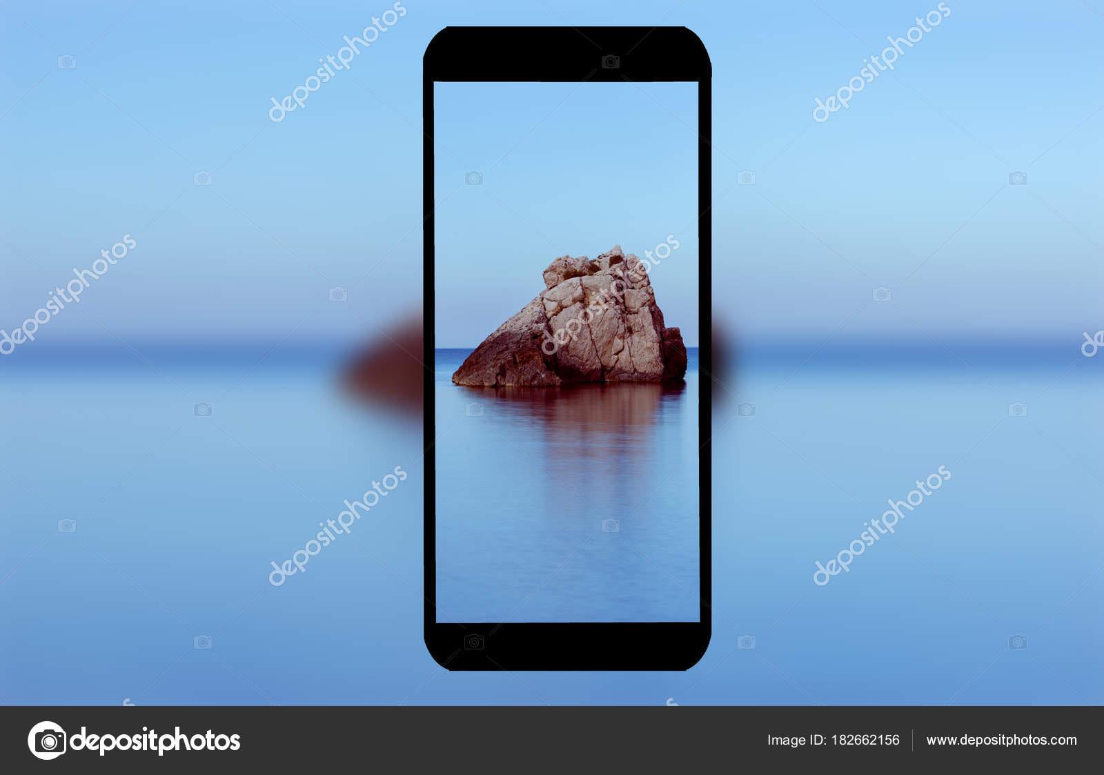 Un Telefono Cellulare Con Il Mare Sullo Sfondo Foto Stock
