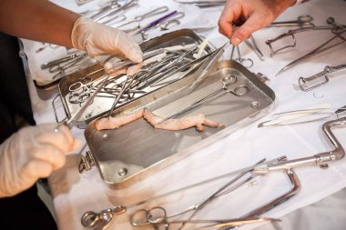 medical courses. surgical tool kit. surgeons sew up body.