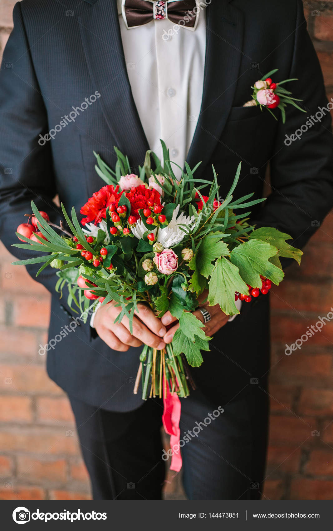 Elegant man dressed in a modern black suit and white shirt holding elegant man dressed in a modern black suit and white shirt holding in hand a wedding flowers bouquet from red carnation close up color vertical image of izmirmasajfo
