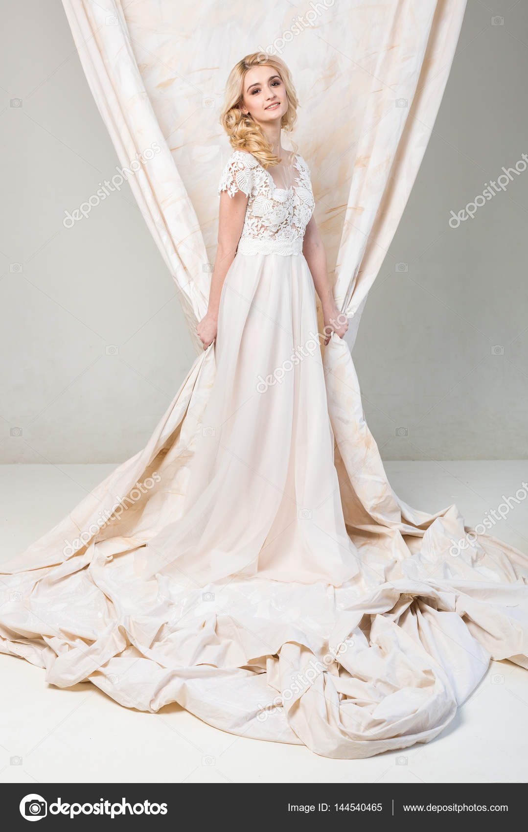 the gorgeous smiling blonde bride with beautiful curly hair in a ...