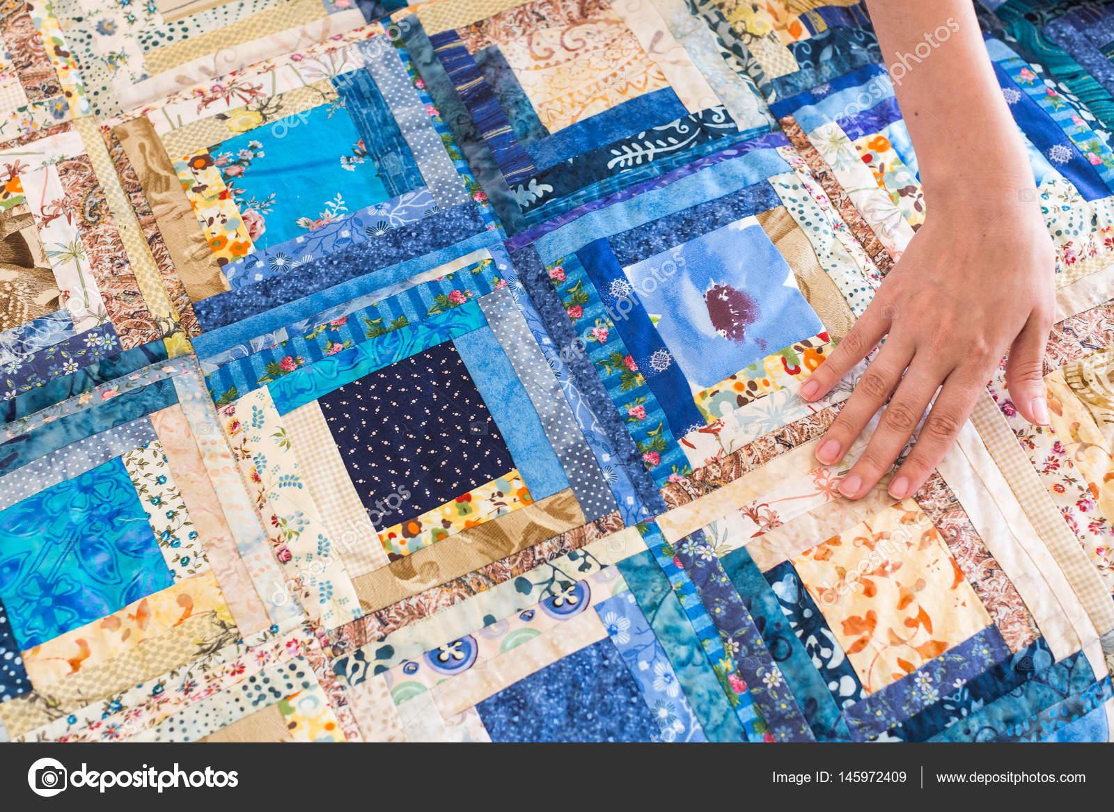 Die kaukasische weibliche Hand berühren Farbe Patchwork quilt mit ...