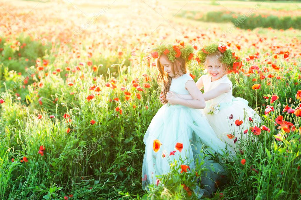 little girl model, wedding, poppies, summer fashion concept - play of two girls in wedding dresses in a sunny field of poppies, the two laughing girls in wreaths of summer flowers, hold hands.