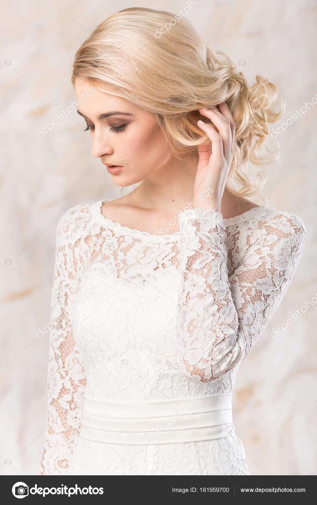 modisches weißes Kleid, schöne blonde Model, Braut-Frisur und Make ...