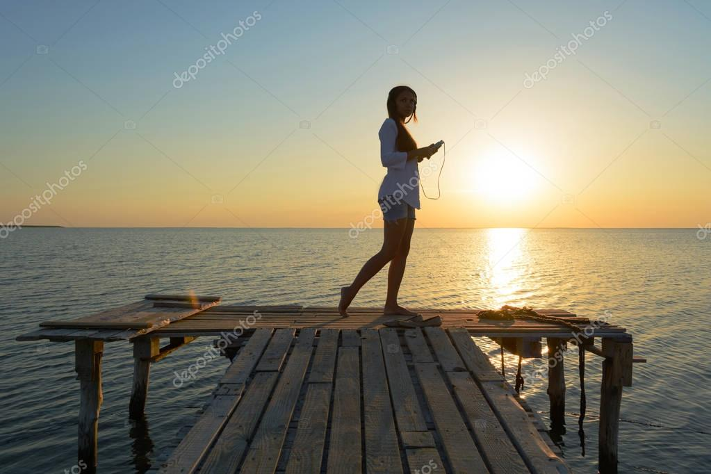Girl in headphones on a bridge by the sea
