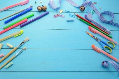 School accessories (pencils, markers, pens, chalk, clips, rivets, scissors, centimeter, ruler) on a wooden blue background (blackboard). Back to school.