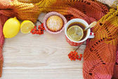 Mug of hot black tea with lemon and homemade cakes (cupcake) on a wooden light background