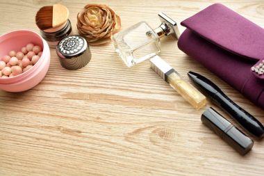 cosmetics (Cream, nail polish, eye shadow, eyebrow, lipstick, lip gloss, blush, powder and perfume) on wooden table