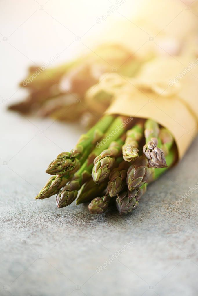 Fresh green asparagus in craft paper on marble background. Banner. Raw, vegan, vegetarian and clean eating concept. Food frame with copy space