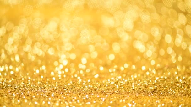 Golden shiny background for Christmas greetings. Banner with defocused lights, bright yellow bokeh. Shimmer of gold glitter texture. Concept of New year, luxury holiday.