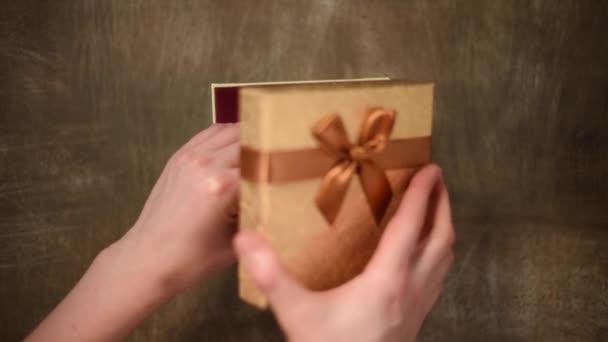 Dámské ruce připravují dárek, překvapení a balení dárkové krabice. Balení dárků. Horní pohled. Koncept Vánoc a Nového roku.