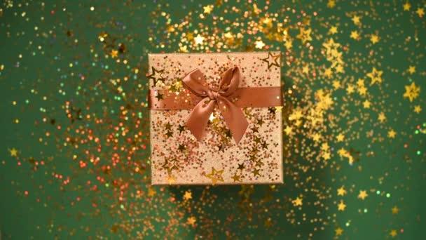Goldglitzernde Sterne, glitzerndes Konfetti über der Geschenkschachtel auf grünem Hintergrund. Ansicht von oben. Weihnachten und Neujahr. Verkauf, Discount-Preis, Einkaufskonzept.