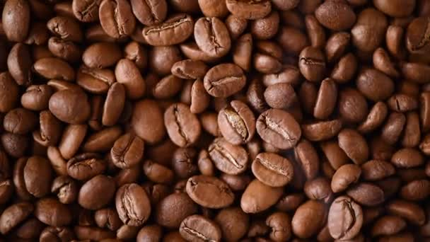 Roasted coffee beans on rorating backgound. Top view. Cappuccino, dark espresso, aroma black caffeine drink, ingredient for coffee beverage.
