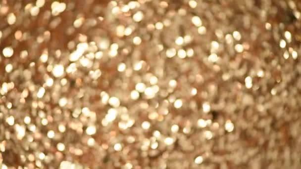 Lesklé abstraktní texturované pozadí se zlatými světly, bokeh. Vánoce, nový rok. Slavnostní zlaté pozadí