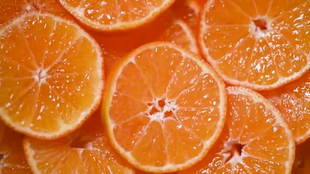 Fresh sliced orange fruit texture on rotating background. Top view. Citrus fruits. Vegan and raw food concept. Juicy oranges background