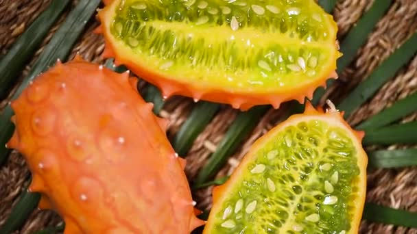 Cuted african horned melon on rotating background. Top view. Exotic Kiwano melon fruits, tropical palm branch. Vegan and raw food concept.