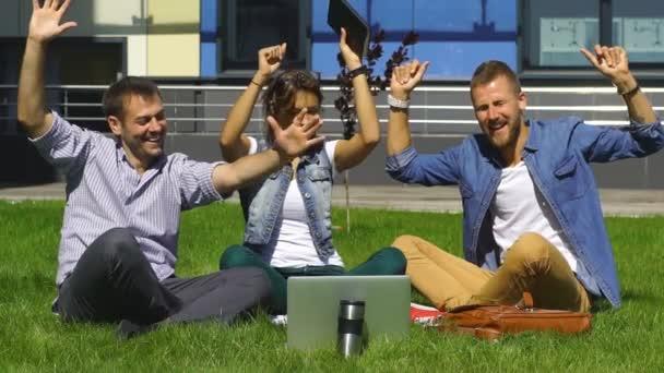 Happy studenti sedí na trávníku a zpívat