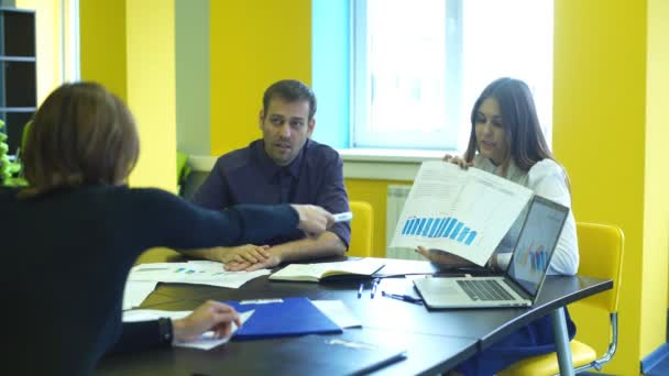three colleagues communicate looking at documents in folders sitting in the office
