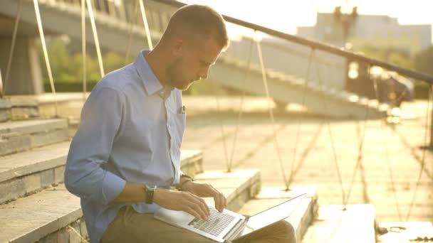 glücklicher Student, der auf seinem Laptop im Internet surft und im Freien sitzt