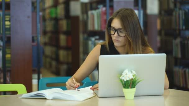 egy lány diák dolgozik a laptop-ban könyvtár