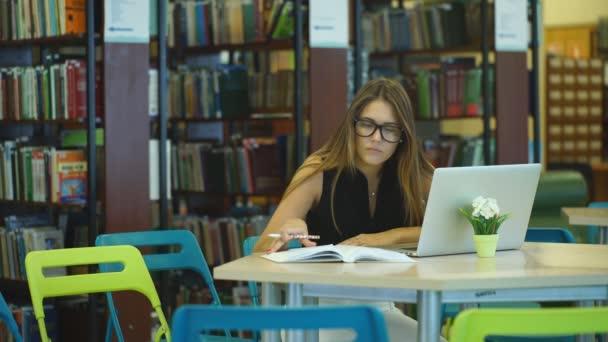 lány diák dolgozik a könyvtárban könyvek és számítógép