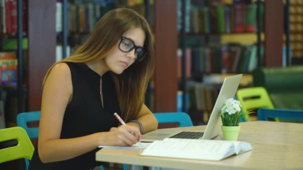 Komoly lány diák dolgozik laptop könyv a városi könyvtárban
