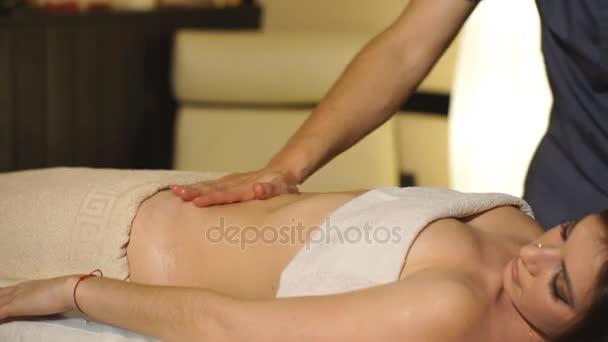 holka dělá břišní masáž s olejem
