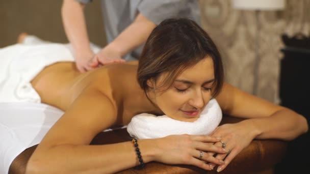 mladá bruneta žena dostává masáž zad