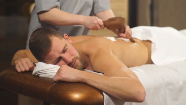 mladý muž dělá masáž pomocí speciální kladivo
