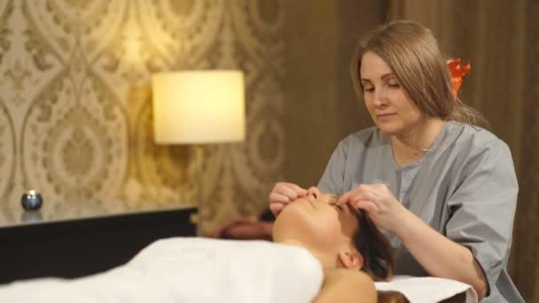 Krásná brunetka dělá obličeje masáž v lázeňském centru