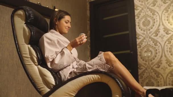 Krásná brunetka v županu sedí na masáž nohou
