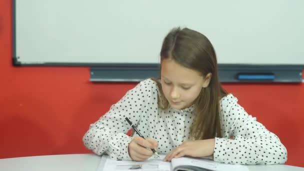 iskola és oktatási koncepció - kis diák lány, aki az iskolában tanul