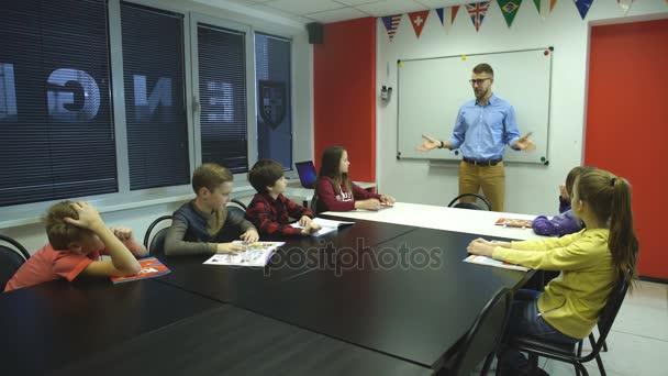Boční pohled na mužský učitel při pohledu na studenty v učebně