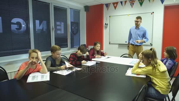 tanulás és az emberek koncepció - segíti iskolai tanár gyerekek tantermi írás teszt