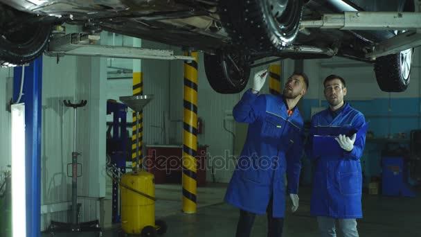 Autószerelő munka alatt egy emelt autó