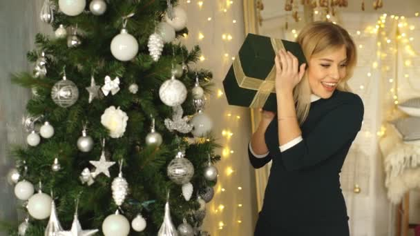blond baví poblíž vánoční stromeček s dárky v rukou