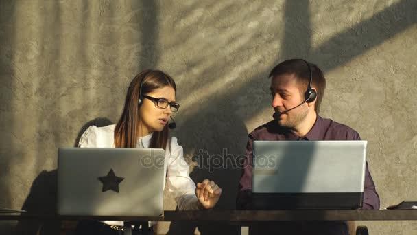 Boční pohled pohledný mladý podnikatel a krásné ženy v sluchátka pomocí přenosných počítačů při práci v kanceláři