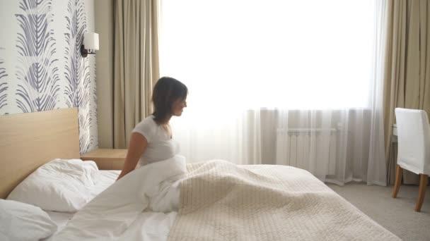 Dobré ráno, mladá žena probudí v posteli