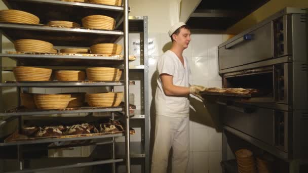 Baker taking a loaf of freshly baked bread from the oven in a modern bakery