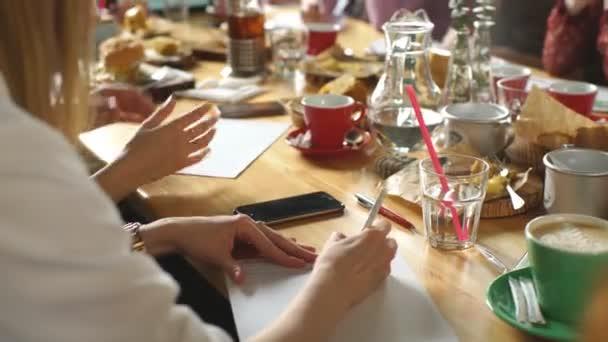 mladá žena, pití kávy a mluvení v café shop