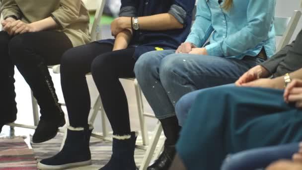 Jsou mladí lidé sedí v kruhu a tleskají při setkání v knihovně moderní