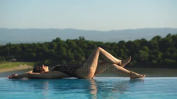 Napozzon a medence szélén a gyönyörű fiatal nő