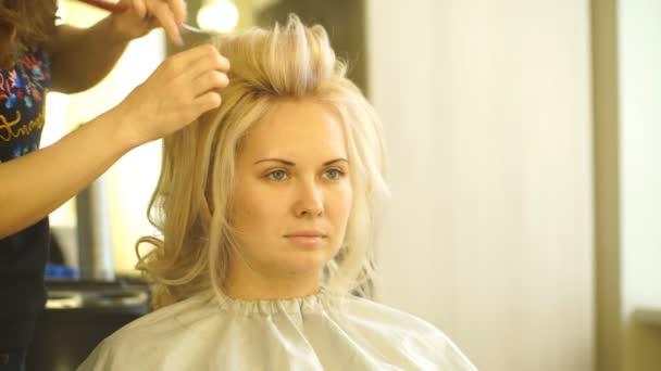 blond holka dělá účes v salonu krásy
