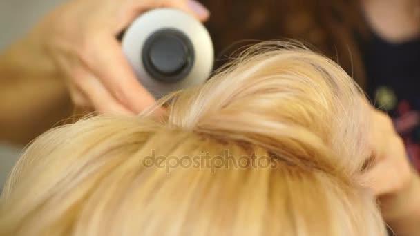 Zlaté vlasy blond holka dělá objem Curling kadeřnice v salónu krásy