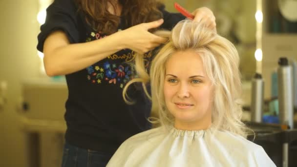 Golden haired blonde girl doing the volume Curling by hairdresser in the beauty salon